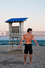 Male lifeguard standing on the beach by a lifeguard stand