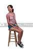 Beautiful young woman stiing on a stool