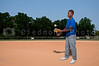 A black African American teenage man baseball pitcher getting ready to throw a ball in a game