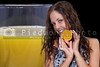 Beautiful woman holding an orange next to a glass of orange juice