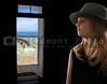 Little girl ooking at the ocean through a beach house doorway