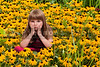 Beautiful little girl sitting in a field of Blackeyed Susans