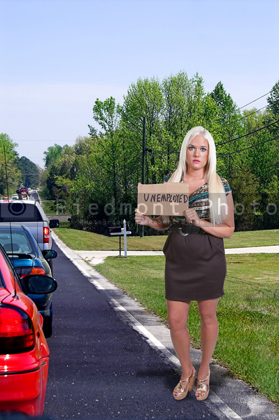 A beautiful young woman holding up an unemployment sign