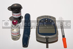 A glucometer, test strips, syringe, insulin and a finger pricking device on a grarduated neutral background