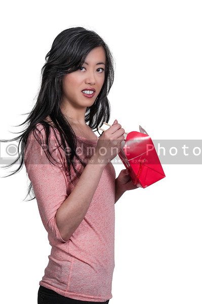A beautiful woman eating Chinese Japanese or Asian takeout food