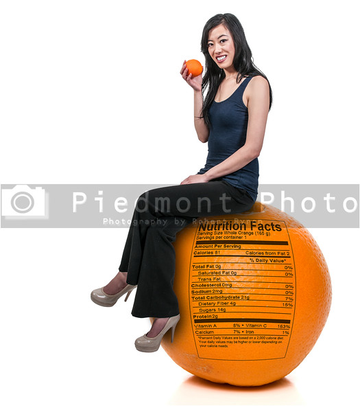 Beautiful young woman sitting on an orange with a nutrition label