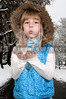 Beautiful little girl blowing snow off of her hands