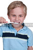 Handsome little boy exercising good dental hygiene by brushing his teeth