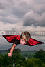 Handsome young boy super hero flying through the sky