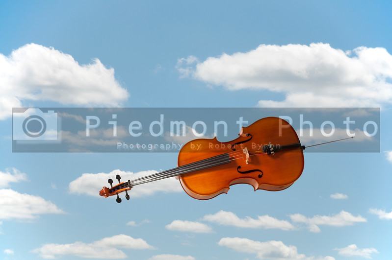 Beautiful wooden musical instrument known as the cello falling or flying through the sky