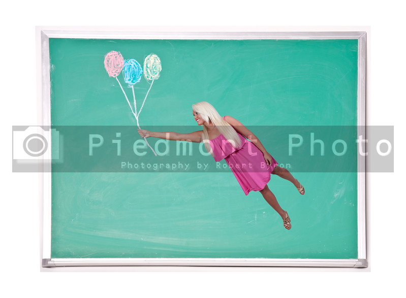 A beautiful young woman floating with balloons on a chalkboard