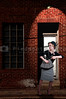 Beautiful scared woman pulling out a gun in a dark alley