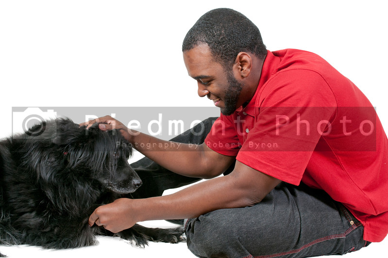 Black African American man playing with a dog