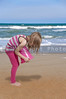 Beautiful little girl playing at the beach