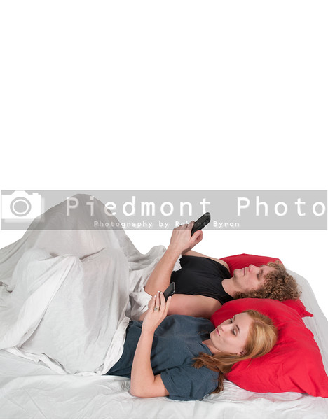 Couple texting in bed