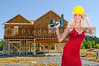 A beautiful woman on a construction site in an evening gown with a hard hat and cordless drill