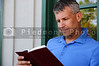A handsome middle aged man reading a book