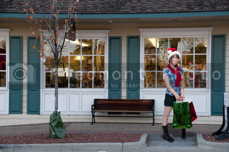 A beautiful young woman holding a bag of Christmas present gifts
