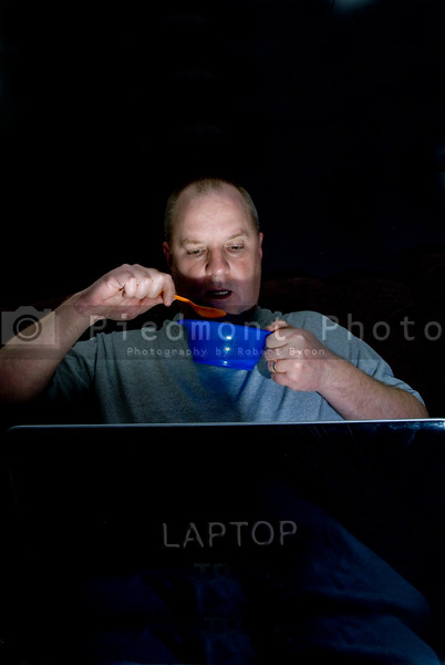 A man having a midnight snack in front of his computer