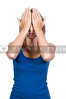A beautiful young scared or surprized woman covering her eyes with her hands