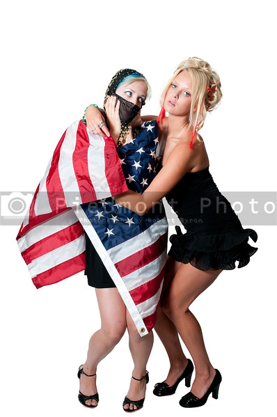 An Arab woman wrapped in an American flag by another woman