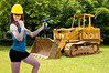 A beautiful woman standing by a large construction bulldozer