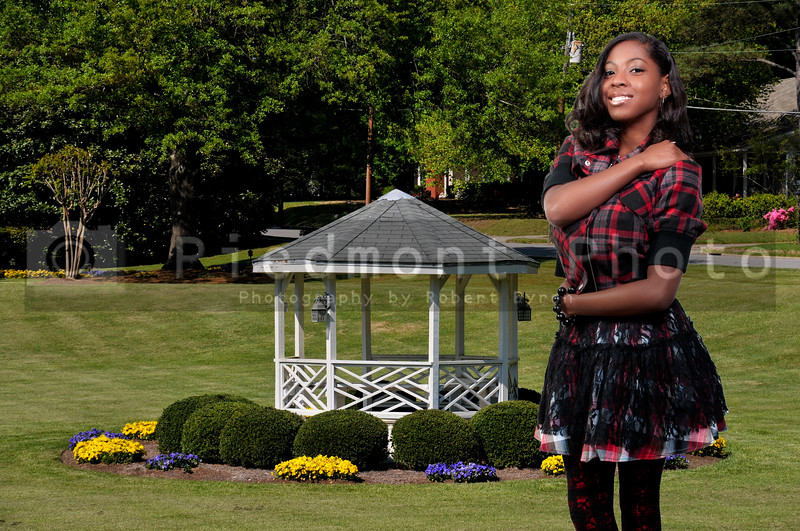An African American teenage girl at a gazebo in a front yard with flowers
