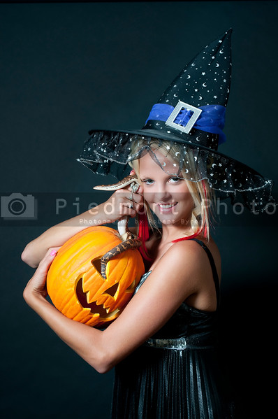 A beautiful young witch with a snake in a jack-o-lantern