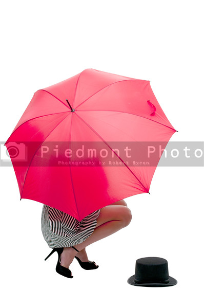 A beautiful woman holding a colorful umbrella with a top hat