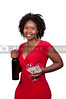 A beautiful African American woman holding wine glasses and a wine bottle