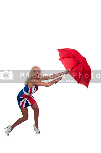 A beautiful woman holding a colorful umbrella in the wind