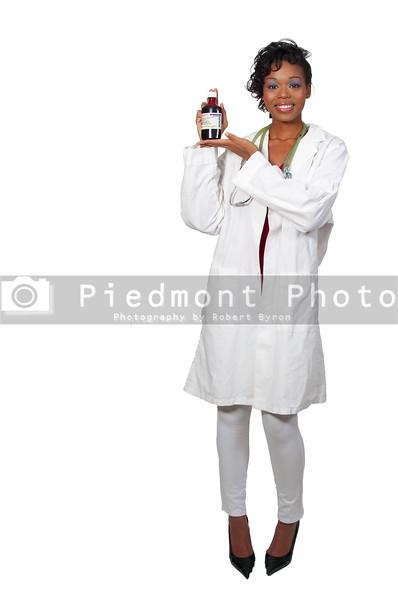 A black woman doctor holding a bottle of prescription medication