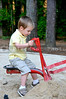 A little boy on a digging machine at a park