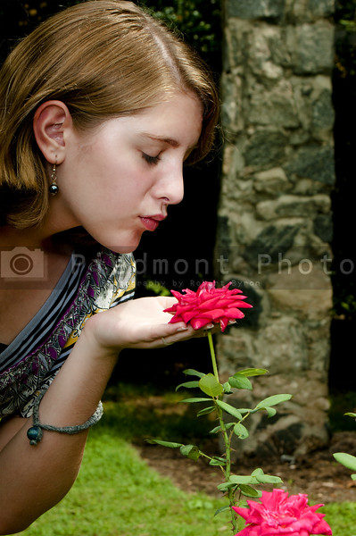 A beautiful Teenage Girl Smelling a Rose