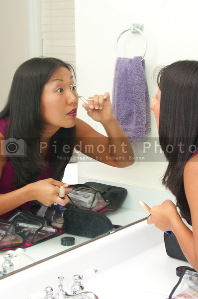 A beautiful woman using a crimper on her eyelashes.