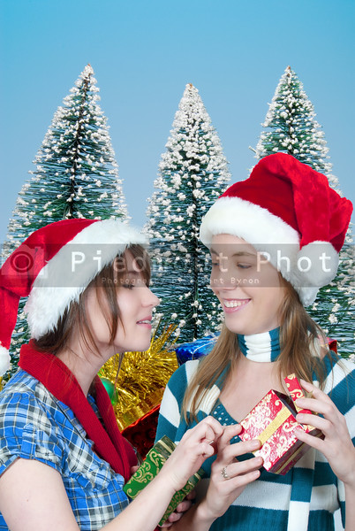 Two beautiful young women exchanging Christmas presents