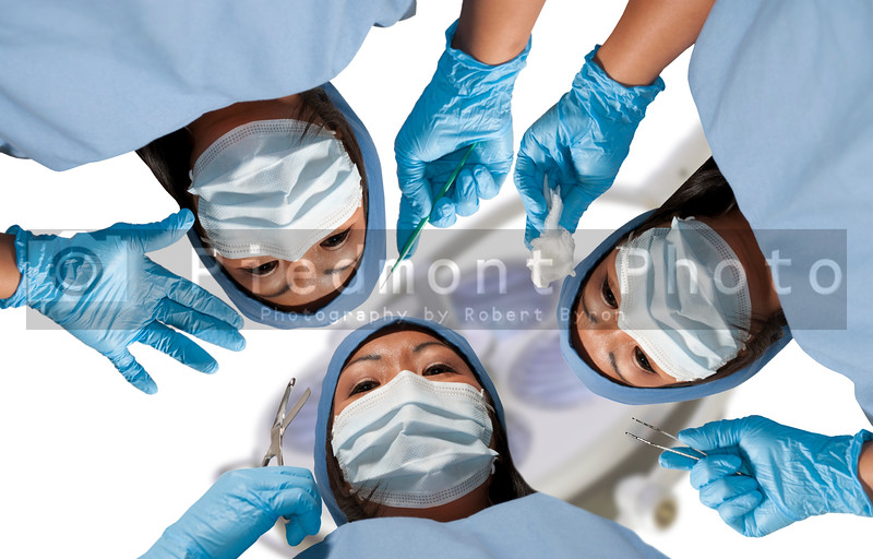 A group of beautiful young woman surgeons performing surgery