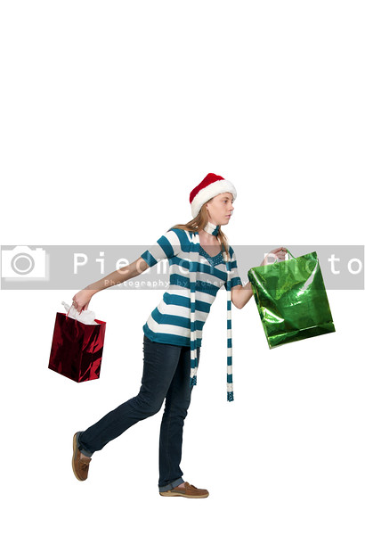 A beautiful young woman holding a bag of Christmas present gifts on a shopping spree