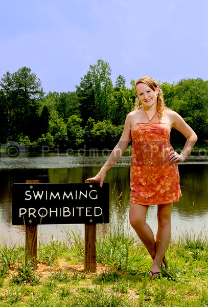 A beautiful woman standing besdide a swimming prohibited sign