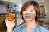 A beautiful young Asian female doctor holding a prescription medicine pill bottle
