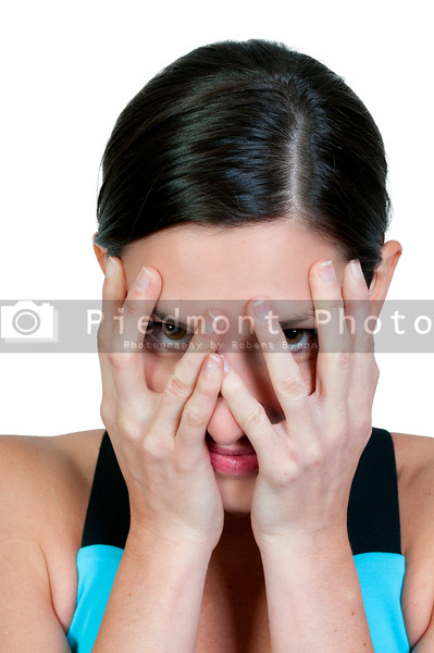 A beautiful young scared or surprized woman looking through her hands