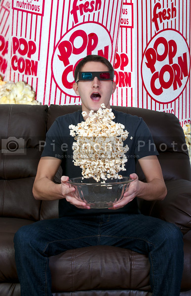 Young man watching a 3d dvd movie on tv at home with popcorn