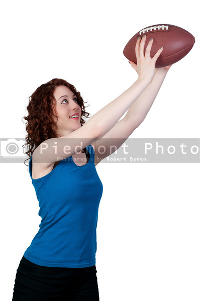 A beautiful young woman catching a football