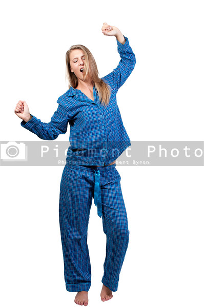 A young yawning and stretching woman waking up in her pajamas in the morning