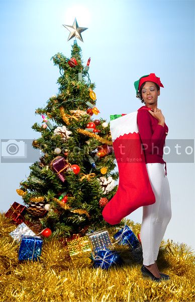 a beautiful woman elf holding a big Christmas stocking