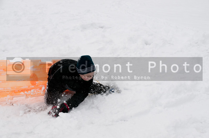 A young boy sledding on a snow covered hill