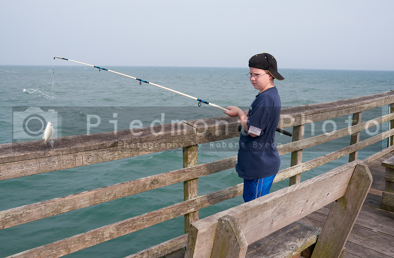 A boy fishing off a pier at the ocean