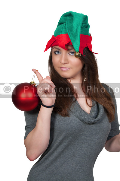 A beautiful young woman elf holding a Christmas Tree Ornament