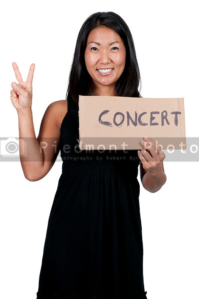 A beautiful Asian woman with a sign hitch hiking to a concert