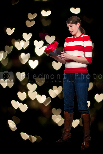 A beautiful young woman holding a Valentines Day heart box gift present